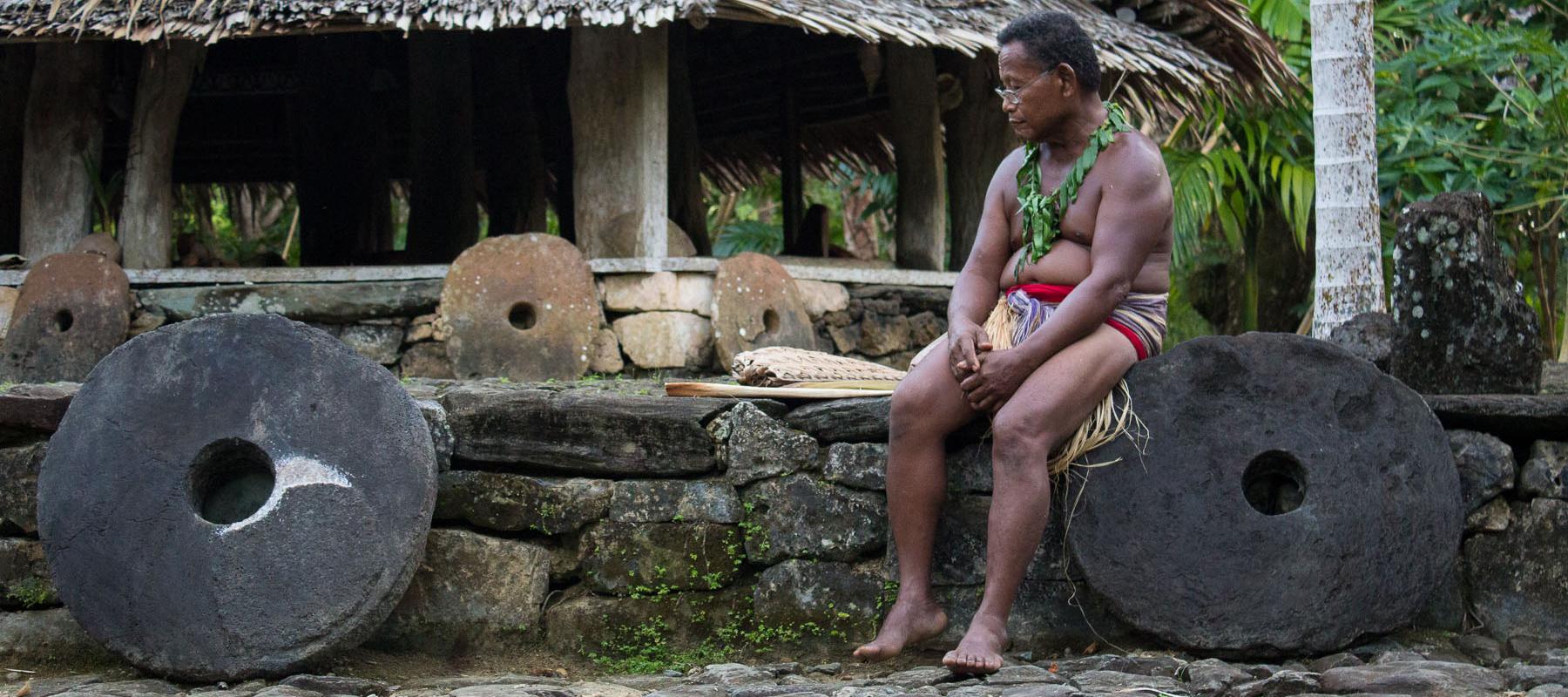 Yapese elder man sitting with stone money at village center